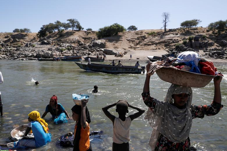 Refugees stand on the Ethiopian bank of a river that separates Sudan from Ethiopia near the Hamdeyat refugees transit camp, which houses Ethiopian refugees fleeing the fighting in the Tigray region, on the Sudan-Ethiopia border, Sudan, November 30. REUTERS/Baz Ratner