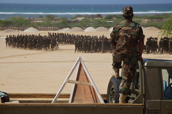 A Somali soldier watches as new recruits for the Somali National Army marches at the passing out parade at Al Jazeera training camp in Mogadishu. 14 August 2012 (Photo by Noe Falk Nielsen/NurPhoto via Getty Images)