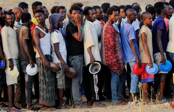 Ethiopian men who fled war in Tigray region, queue for wet food ration at the Um-Rakoba camp, on the Sudan-Ethiopia border in Al-Qadarif state, Sudan November 19, 2020. (Reuters)