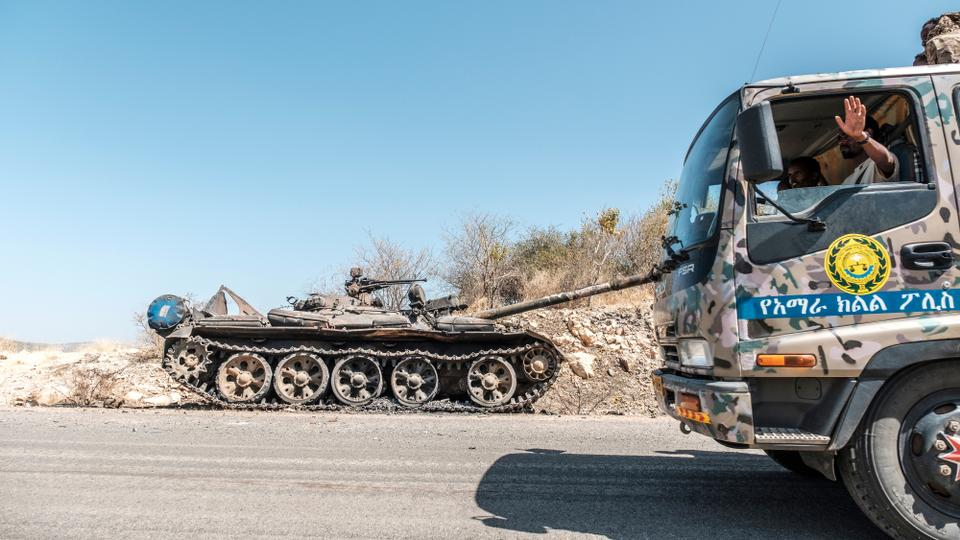 A damaged tank stands abandoned on a road as a truck of the Amhara Special Forces passes by near Humera, in Ethiopia, on November 22, 2020. (AFP)