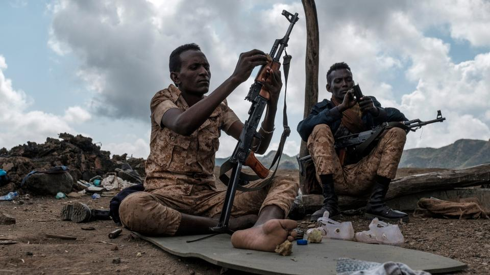 Members of the Afar Special Forces clean their weapons next to a damaged house on the outskirts of the village of Bisober, Tigray Region, Ethiopia, on December 09, 2020. (AFP)