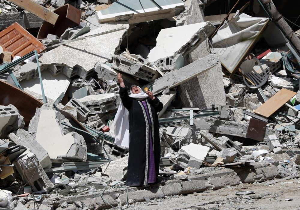 A woman reacts while standing near the rubble of a building that was destroyed by an Israeli airstrike on Saturday that housed The Associated Press, broadcaster Al-Jazeera and other media outlets, in Gaza City, Sunday, May 16, 2021. (AP Photo/Adel Hana)