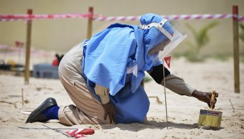 A member of an Explosive Ordnance Disposal team brushes sand off a mortar shell during a demonstration held by the United Nations Mine Action Service (UNMAS) in Mogadishu, Somalia. Credit: UN Photo/Tobin Jones