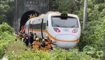 In this photo released by the Executive Yuan, rescue workers gather near one end of the train involved in a derailment near the Taroko Gorge area in Hualien, Taiwan on Friday, April 2, 2021. The train partially derailed in eastern Taiwan on Friday after colliding with an unmanned vehicle that had rolled down a hill, killing dozens. With the train still partly in a tunnel, survivors climbed out of windows and walked along the train's roof to reach safety after the country's deadliest railway disaster. (Executive Yuan via AP)