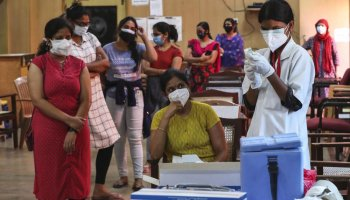 An Indian nurse prepares to administer a dose of Covishield, Serum Institute of India's version of the AstraZeneca vaccine to a woman as others wait their turn in Bengaluru, India, Wednesday, May 19, 2021. India has the second-highest coronavirus caseload after the U.S. with more than 25 million confirmed infections. (AP Photo/Aijaz Rahi)